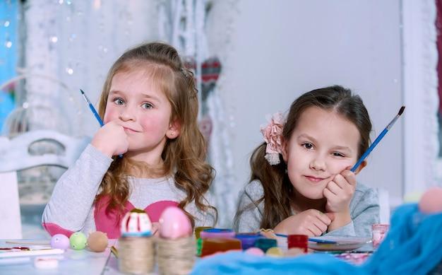 Due bambine con i pennelli in mano pensando e non sanno cosa disegnano. concetto di crisi creativa. Foto Premium