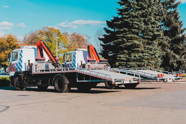 Due nuovi carri attrezzi parcheggiati vicino alla strada in città. gru su camion per rimorchio di automobili. urbano. servizio. vista laterale. riguarda i sollevatori Foto Premium