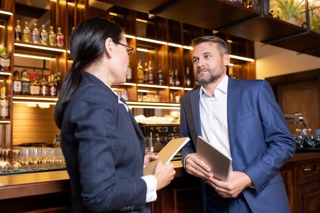 Due proprietari di un lussuoso ristorante in piedi al bancone del bar e consultando alcuni momenti di lavoro Foto Premium