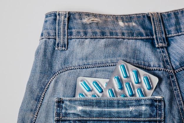 Due confezioni di capsule blu nella tasca dei pantaloni. pillole per la salute dell'uomo e l'energia sessuale nei jeans. Foto Premium