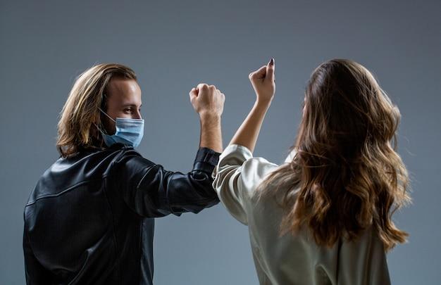 Due persone sbattono i gomiti. epidemia di coronavirus. amici in maschera di sicurezza. le giovani coppie indossano maschere per il viso. ragazza e ragazzo saluto con i gomiti. nuova vita reale. quarantena per il coronavirus. urto dei gomiti. Foto Premium