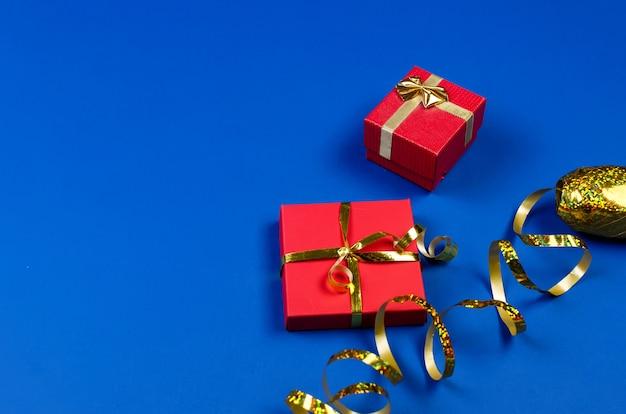 Due scatole regalo rosse con nastro dorato su sfondo blu. Foto Premium
