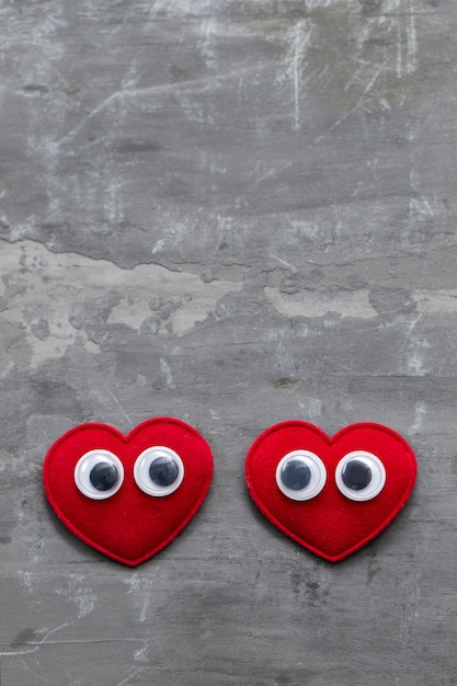 Due cuori rossi con occhi su fondo in ceramica Foto Premium