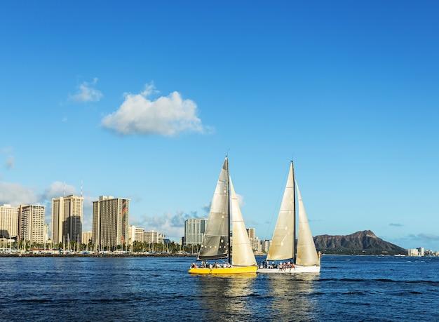 Due barche a vela in mare con sfondo diamond head montagna, honolulu hawaii Foto Premium