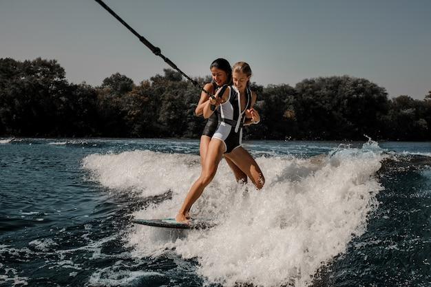 Due donne sexy che praticano il surfing su un bordo giù l'acqua blu Foto Premium