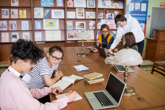 Due piccoli gruppi di studenti universitari contemporanei seduti ai banchi e discutere i loro piani o punti di progetti in biblioteca Foto Premium
