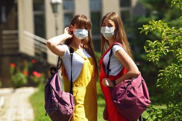 Due gemelli adolescenti in un abito scolastico giallo e rosso con zaini viola vanno a scuola a piedi Foto Premium