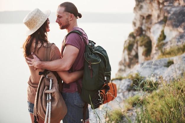 Due maschio e una donna turistica con gli zaini stanno alla cima della montagna e godono dell'alba. concetto di vacanze avventura stile di vita di viaggio Foto Premium
