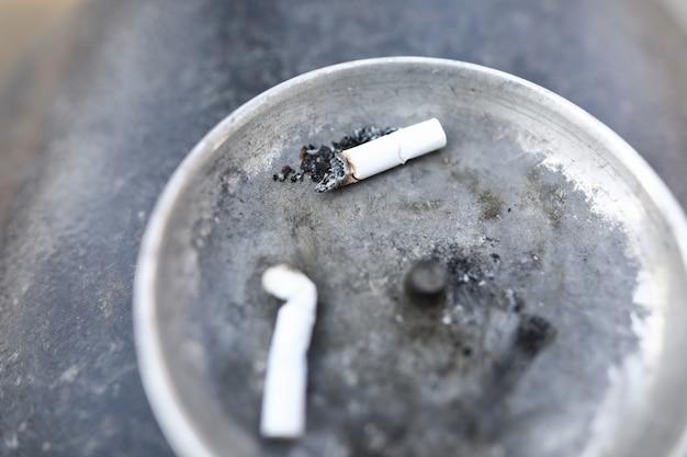 Due mozziconi di sigaretta bianchi che giace nel portacenere Foto Premium