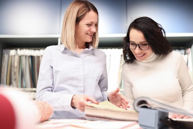 Due donne selezionano i tessuti dai campioni. atelier per la sartoria e la riparazione del concetto di abbigliamento Foto Premium