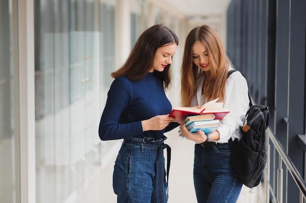 Due giovani studentesse in piedi con libri e borse nel corridoio Foto Premium