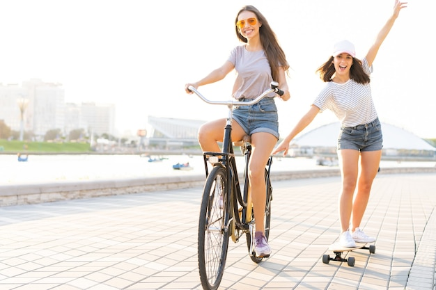 Due giovani amici che si rilassano in una calda giornata estiva con una giovane donna in bicicletta che rimorchia la sua amica su uno skateboard lungo una strada urbana Foto Premium