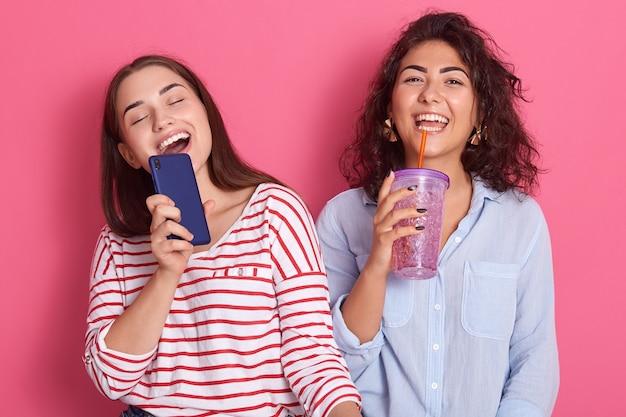 Due giovani ragazze caucasiche felici ed emozionate che cantano insieme la canzone in linea di karaoke con il telefono ed il cocktail come il microfono Foto Premium