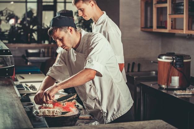 Due giovani chef bianchi vestiti in uniforme bianca decorano il piatto pronto nel ristorante Foto Premium
