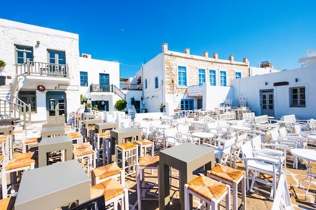 Tipica taverna greca con tavoli e sedie colorate nel porto di naoussa Foto Premium