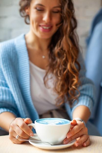 Donna felice sfocata con capelli ondulati lunghi in maglione caldo che tiene tazza di latte blu caldo. bevanda e colore alla moda. il latte del tè blu è fatto con fiori di pisello farfalla. bevanda salutare a base di erbe Foto Premium