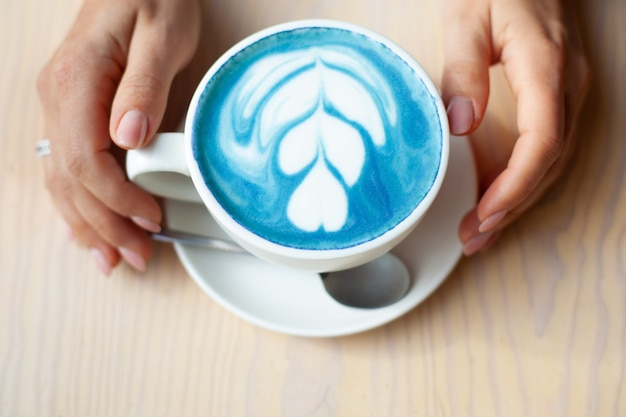 Mani sfocate della donna che tengono la tazza del latte caldo del pisello della farfalla o del latte blu della spirulina sulla tavola di legno. bevanda biologica sana e alla moda. concetto di benessere e disintossicazione. copia spazio. Foto Premium