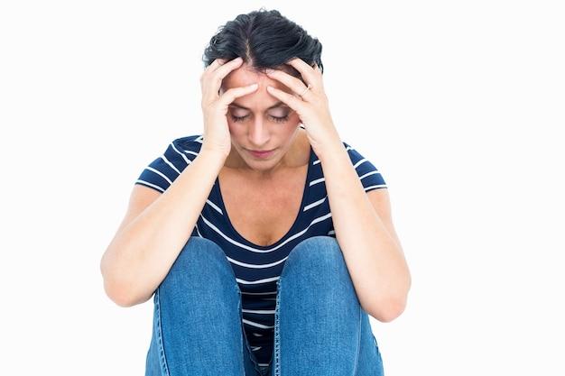 Donna infelice che si siede sul pavimento Foto Premium
