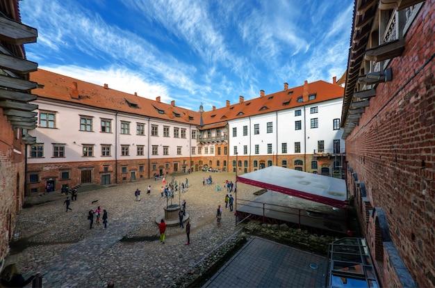 Persone non identificate camminano vicino al castello di mir nella regione di grodno, bielorussia. il castello è una fortificazione difensiva del xvi-xvii secolo Foto Premium