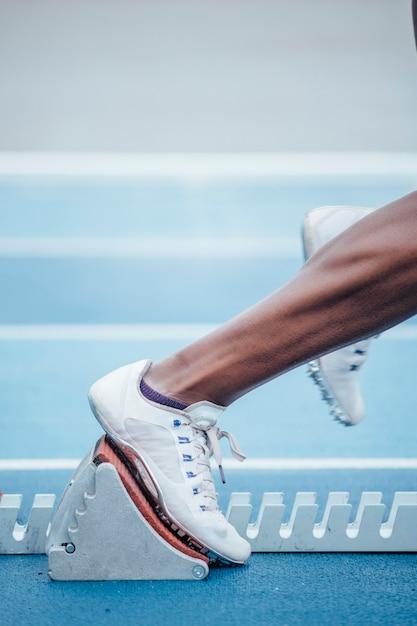 Irriconoscibile afro sportiva in abbigliamento sportivo che inizia la corsa dalla posizione di partenza accovacciata sui blocchi di partenza Foto Premium