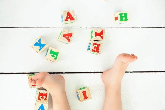 Bambina irriconoscibile che gioca con i cubi di abc all'interno. lettere sul pavimento. sfondo di scuola Foto Premium
