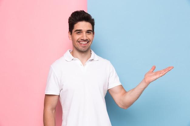 Ragazzo con la barba lunga in t-shirt casual sorridente e gesticolando mano da parte a copyspace, isolato su un muro colorato Foto Premium
