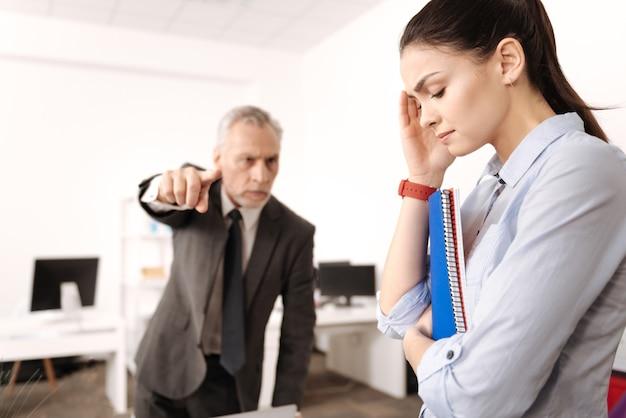 Donna sconvolta chinando la testa abbracciando i documenti mentre si trova in posizione semi in primo piano Foto Premium