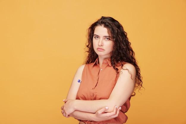 Ragazza malata sconvolta con i capelli ricci in piedi con le braccia incrociate mentre misura la temperatura corporea, controllo del coronavirus Foto Premium