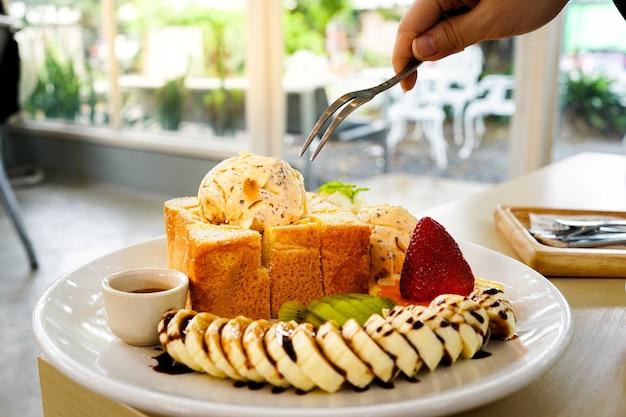 Usa la forchetta per mangiare pane tostato al miele servito con frutta mista, banana a fette, gelato Foto Premium