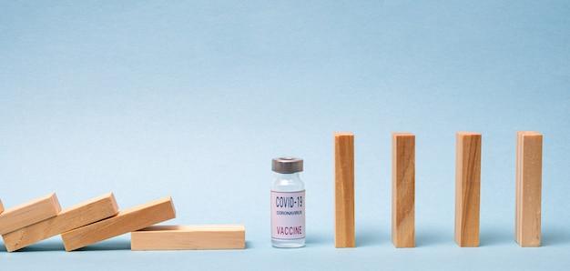 Concetto di vaccino con domino in legno e fiala di vaccino covid-19 su sfondo blu. Foto Premium