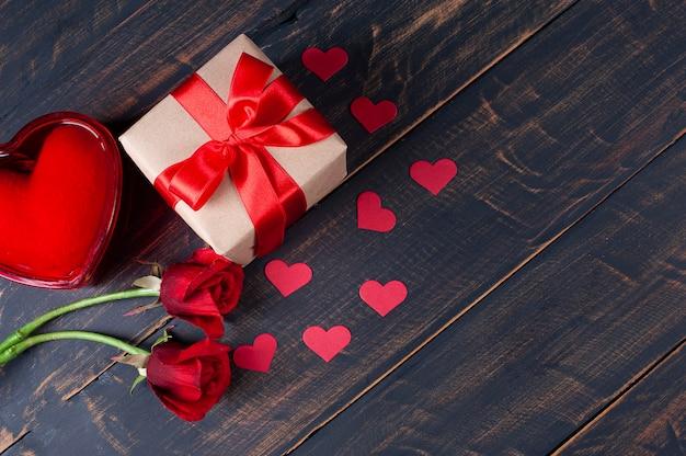 San valentino. decorazione con scatola regalo, cuori rossi e fiori su fondo di legno rustico Foto Premium