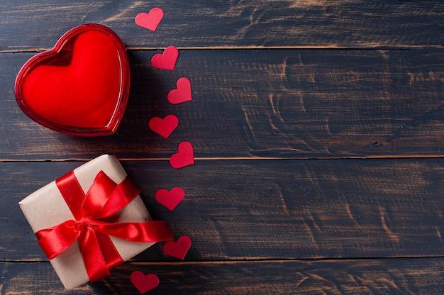 San valentino. decorazione con scatola regalo, cuori rossi su fondo di legno rustico Foto Premium