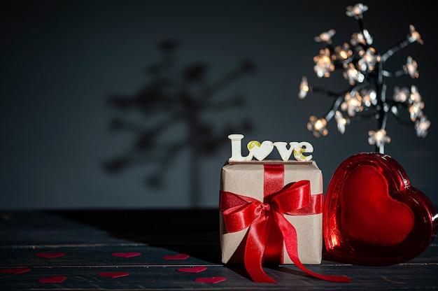 San valentino. decorazione con la parola amore e confezione regalo e cuori rossi Foto Premium
