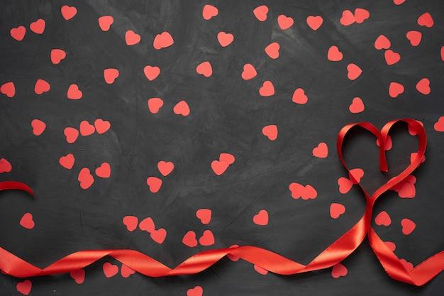 Biglietto di auguri di san valentino. nastro rosso a forma di cuore su fondo di pietra. vista dall'alto con copia spazio Foto Premium