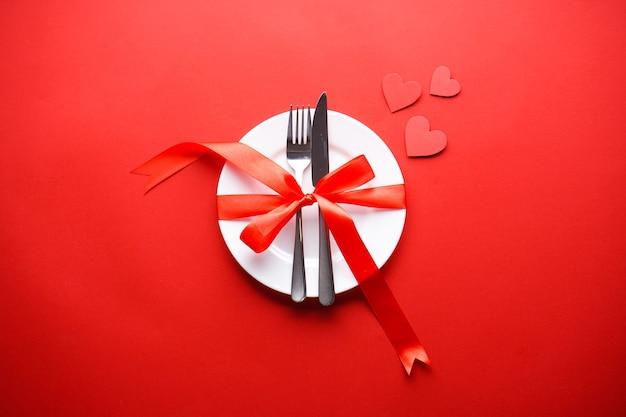 San valentino. concetto di amore. festa della mamma. cuori con posate su un piatto bianco con un nastro rosso su sfondo rosso, piatto laici. Foto Premium