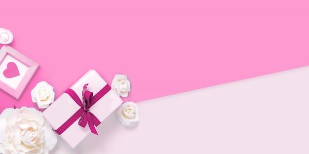 San valentino sfondo con confezione regalo, fiori e cuore rosa Foto Premium