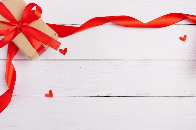 Confezione regalo di san valentino, cuori e nastro su fondo di legno bianco, spazio della copia Foto Premium