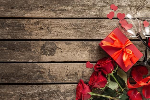 San valentino o festa della mamma scatola regalo rosso con fiori di carta cuori e bicchieri di vino su fondo in legno vista dall'alto Foto Premium