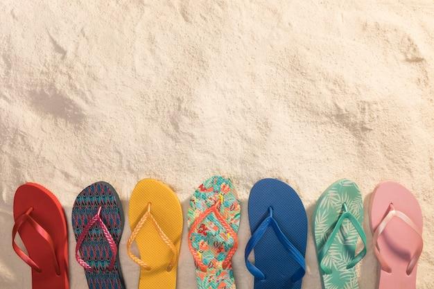 Varietà di sandali infradito colorati sulla sabbia Foto Premium