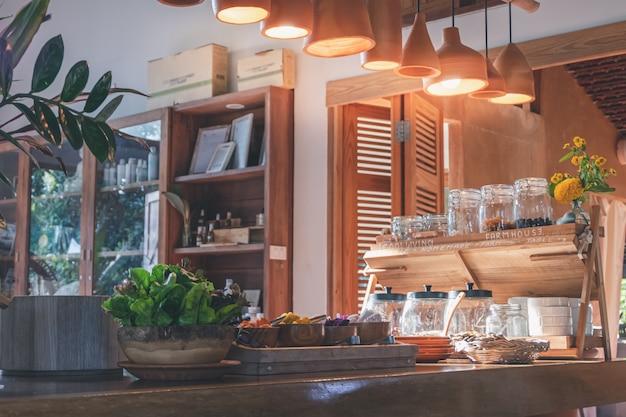 Varietà di grano e semi di piante con piante di insalata e condimento di alimenti sani in ciotola di legno sul tavolo di legno Foto Premium
