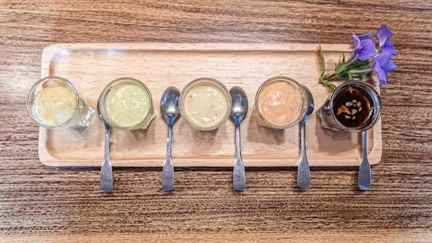 Varietà di condimento per l'insalata sulla tavola di legno Foto Premium