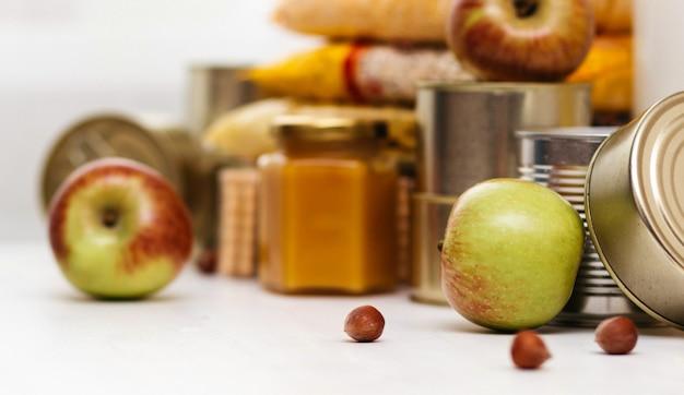 Varie conserve, pasta e cereali su un tavolo bianco. donazione di cibo o concetto di consegna di cibo. Foto Premium