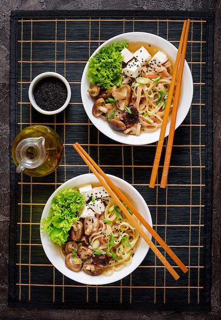 Minestra di pasta vegana con formaggio tofu, funghi shiitake e lattuga in ciotola bianca. cibo asiatico. vista dall'alto. disteso Foto Premium