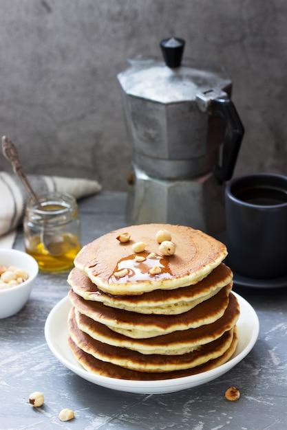 Colazione vegetariana a base di pancake, caffè, miele, noci e frutta. Foto Premium