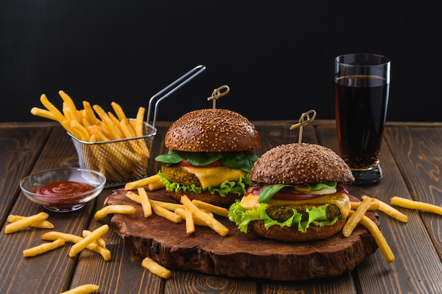 Hamburger vegetariano con patatine fritte e bevande sul tavolo di legno Foto Premium
