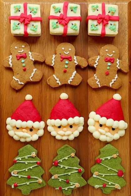 Immagine verticale di biscotti di natale fatti in casa assortiti isolati su breadboard in legno Foto Premium