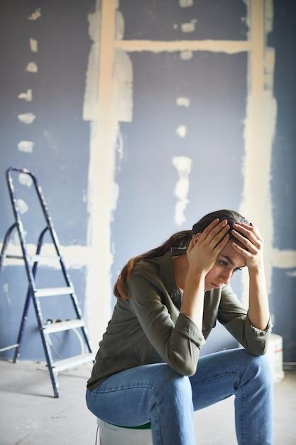 Ritratto verticale di giovane donna frustrata devastata dal progetto di ristrutturazione che si siede sul barattolo di vernice contro il muro a secco, copia dello spazio Foto Premium