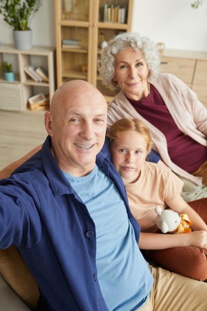Ritratto verticale della moderna coppia senior tenendo selfie con carina ragazza dai capelli rossi in interni domestici Foto Premium