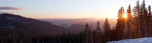 Vista dall'alto affascinante paesaggio pittoresco di catene montuose ricoperte da fitte e innevate foreste di abeti contro il sole al tramonto in una limpida sera d'inverno Foto Premium