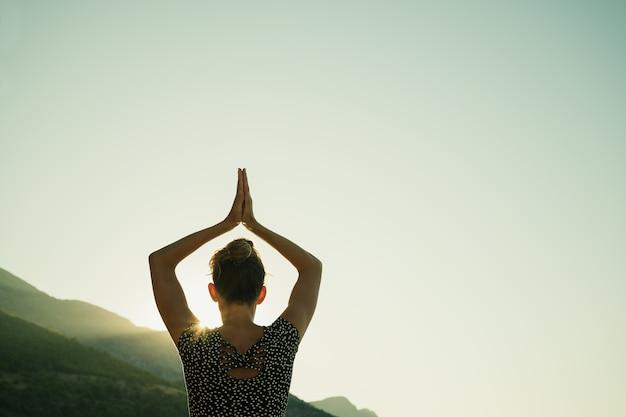 Vista da dietro di una giovane donna che fa una posa di assana con le braccia unite sopra la testa mentre fa il suo allenamento yoga mattutino all'alba. Foto Premium
